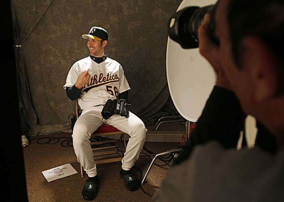 Oakland Athletics starting pitcher Justin Duchscherer, left, laughs while being photographed by the A's team photographer Michael Zagaris, right, during picture day at spring training baseball in Phoenix,  Monday, March 1, 2010. Photo: Eric Risberg, AP