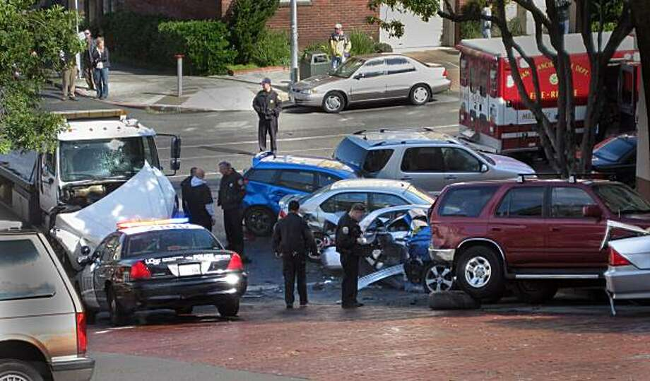 A runaway tow truck (top right) sits at the bottom of Third Avenue at Irving Street after it had crashed into at least 10 parked cars Monday in San Francisco's Inner Sunset neighborhood, causing two injuries, authorities said. The crash happened on Third Avenue between Irving Street and Parnassus Avenue at about 10:30 a.m. when a tow truck with a car that was being off-loaded began rolling backward on the hilly street, said Officer Samson Chan, a Police Department spokesman. John Barretto/Special to the Chronicle Photo: John Barretto, The Chronicle