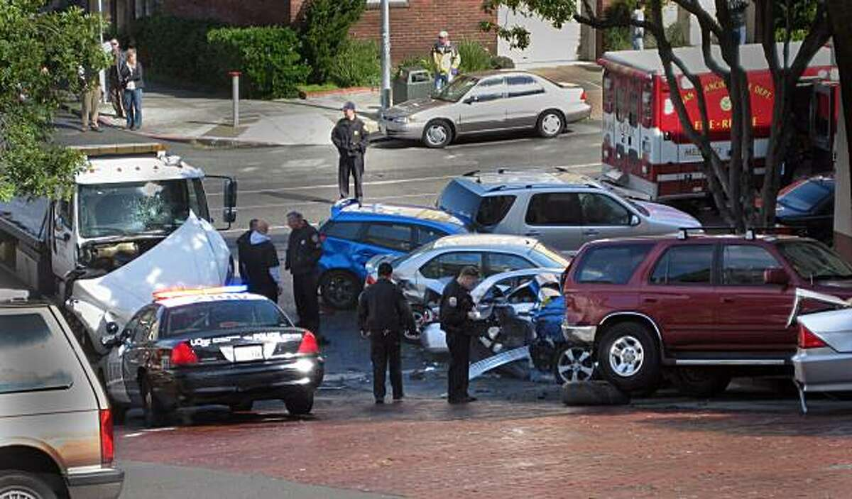 A runaway tow truck (top right) sits at the bottom of Third Avenue at Irving Street after it had crashed into at least 10 parked cars Monday in San Francisco's Inner Sunset neighborhood, causing two injuries, authorities said. The crash happened on Third Avenue between Irving Street and Parnassus Avenue at about 10:30 a.m. when a tow truck with a car that was being off-loaded began rolling backward on the hilly street, said Officer Samson Chan, a Police Department spokesman. John Barretto/Special to the Chronicle