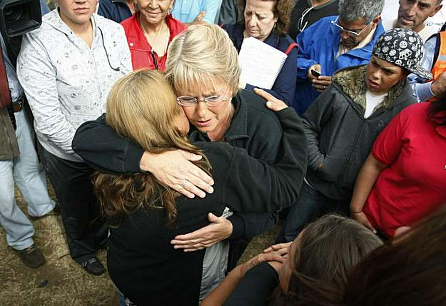 Chile's President Michelle Bachelet, center, embraces an earthquake victim during an inspection visit to Iloca, Chile, Saturday, March 6, 2010 . An 8.8-magnitude earthquake hit central Chile last Feb. 27, causing widespread damage. Photo: Fernando Vergara, AP