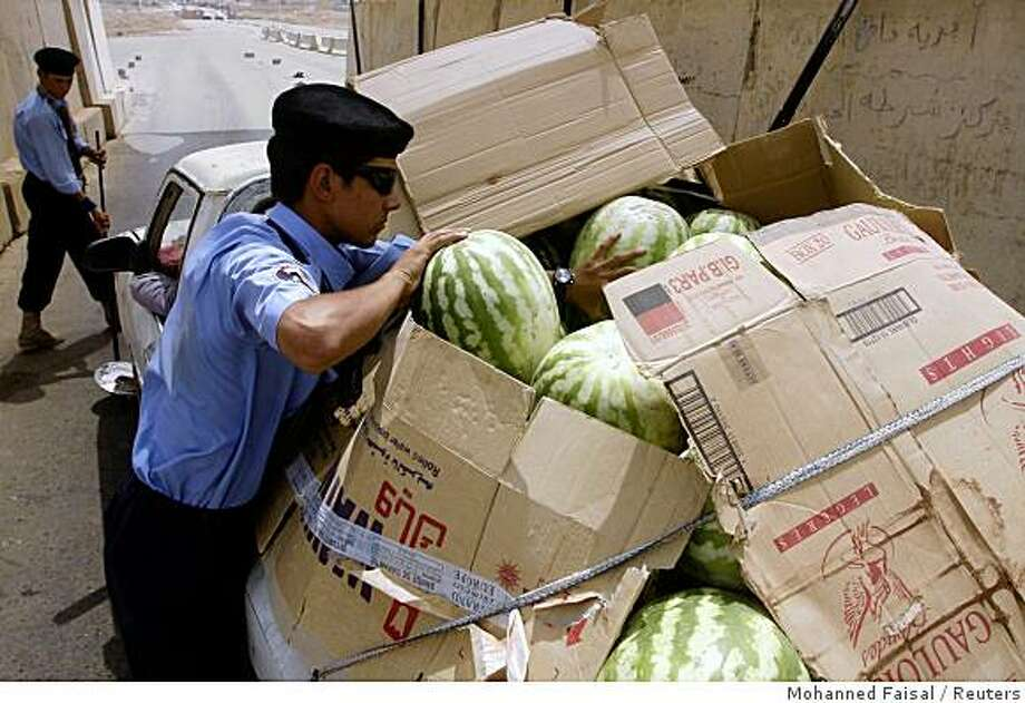Police check a vehicle transporting watermelons at a checkpoint on a highway in Ramadi, 100 km (60 miles) west of Baghdad, August 31, 2008. U.S. troops will on September 1 hand over control of Iraq 's Anbar province, once the heart of a bloody Sunni Arab insurgency, reflecting a dramatic drop in violence across the country, an Iraqi official said on Thursday. REUTERS/Mohanned Faisal (IRAQ) Photo: Mohanned Faisal, Reuters