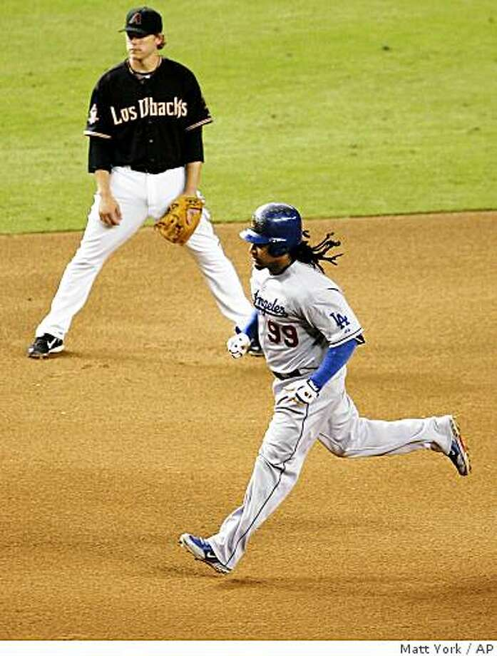 Los Angeles Dodgers' Manny Ramirez approaches third base after hitting a solo home run against the Arizona Diamondbacks during the seventh inning of a baseball game Saturday, Aug. 30, 2008, in Phoenix. At rear is Diamondbacks' Mark Reynolds. (AP Photo/Matt York) Photo: Matt York, AP