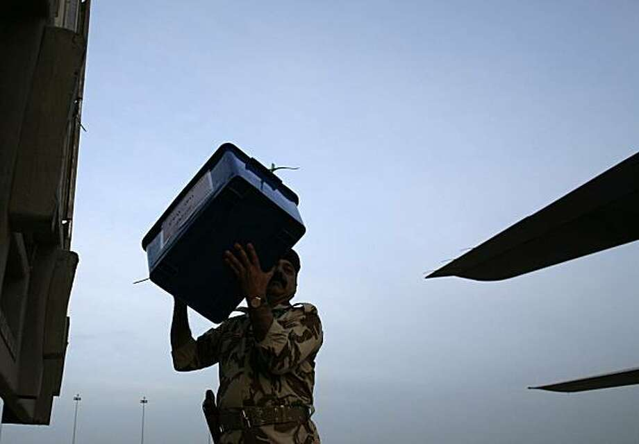 An Iraqi Army soldier carries a box of ballot tally sheets from Ninevah province for the national election to an Iraqi military cargo plane bound for Baghdad in Mosul, north of Baghdad, Iraq, Monday, March 8, 2010. Photo: Maya Alleruzzo, AP