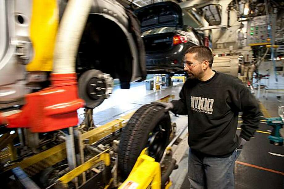 A NUMMI plant worker guides a wheel into position to be automatically attached to a Toyota Corolla as it passes by on the assembly line on March 4, 2010, in Fremont, CA. Photo: Chad Ziemendorf, Special To The Chronicle