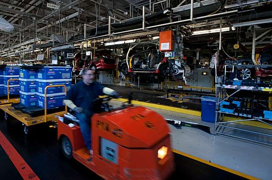 "Everyone and everything is in constant motion at the NUMMI plant in Fremont, CA.  A service truck carries supplies on a designated ""roadway"" while Toyota Corollas move down the assembly line in the background on March 4, 2010. Photo: Chad Ziemendorf, Special To The Chronicle"