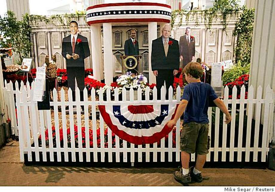 A boy looks over a presidential display, including life size photographic cutouts of presidential candidates Barack Obama (D-IL) (L) and John McCain (R-AZ) (R), at the Minnesota State Fair in St. Paul, Minnesota, August 30, 2008. The 2008 Republican National Convention is scheduled to begin in St. Paul, Minnesota, September 1, 2008.   Picture taken August 30, 2008. REUTERS/Mike Segar   (UNITED STATES)   US PRESIDENTIAL ELECTION CAMPAIGN 2008 (USA) Photo: Mike Segar, Reuters