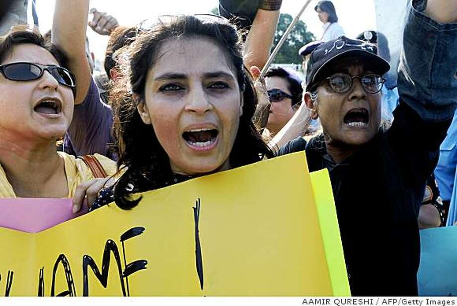 Pakistani human rights activists shout slogans during a protest in front of the Parliment House in Islamabad on September 2, 2008, over the honour killing. Pakistani police have arrested four suspects and launched an investigation into the deaths of three women thought murdered in the name of family honour last month in Babakot village, 450 kilometres southeast of Quetta, for marrying men of their choice. More than 4,000 people, mostly women, have been killed in conservative rural areas of Pakistan in recent years in the name of family honour.   AFP PHOTO/Aamir QURESHI (Photo credit should read AAMIR QURESHI/AFP/Getty Images) Photo: AAMIR QURESHI, AFP/Getty Images