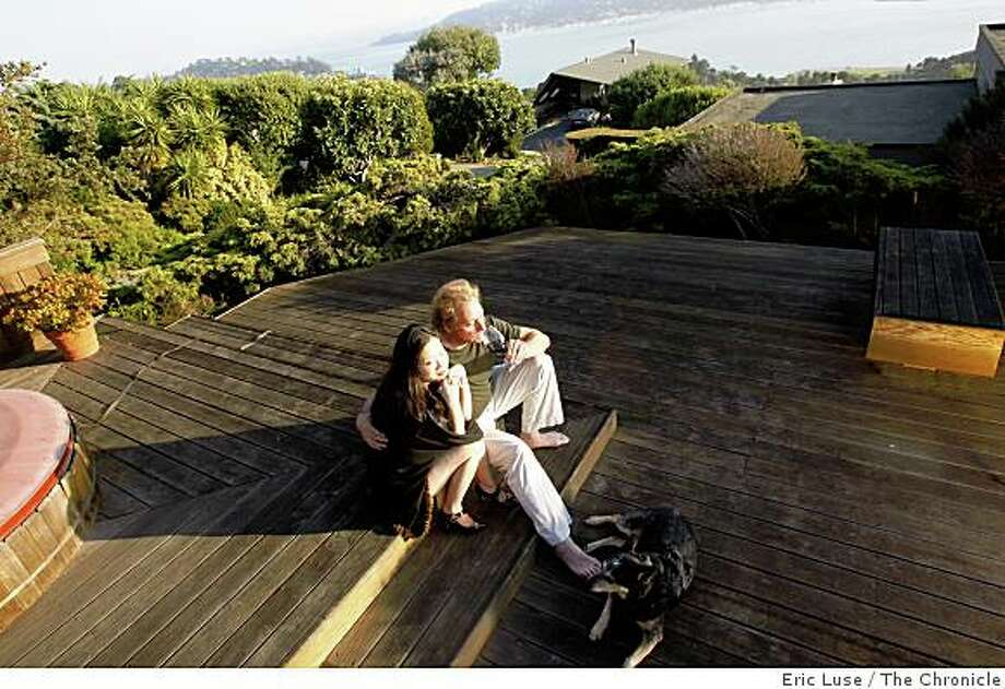 Anyi Lu, shoe designer, with her husband David Spatz and family dog Skippy on their back deck, which overlooks the bay. Photo: Eric Luse, The Chronicle