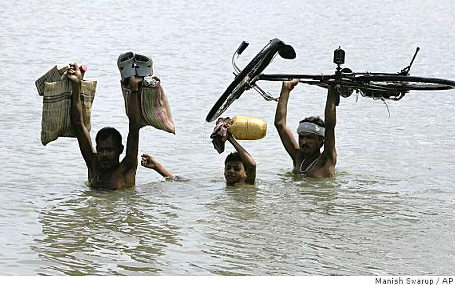 Villagers wade through floodwaters towards safer areas near Saharsa, about 280 kilometers (175 miles) northeast of Patna, India, Tuesday, Sept. 2, 2008. Indian authorities rushed doctors and medical equipment to flood-devastated northern India on Monday to ward off outbreaks of disease among the hundreds of thousands of victims crowding relief camps, officials said. (AP Photo/Manish Swarup) Photo: Manish Swarup, AP
