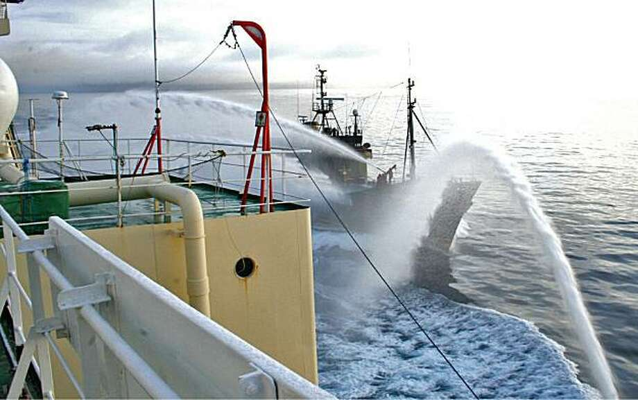 ** THIS CORRECTS THE SOURCE IN HEADER FIELD ** In this photo taken Wednesday, Feb. 17, 2010 released by the Institute of Cetacean Research of Japan, anti-whaling group Sea Shepherd's ship Steve Irwin, background, and the Japanese whaling ship Nisshin Maruuse water cannons to each other in Antarctic Sea. The U.S.-based activist group, sends vessels to confront the Japanese fleet each year, trying to block them from firing harpoons at the whales. Photo: AP