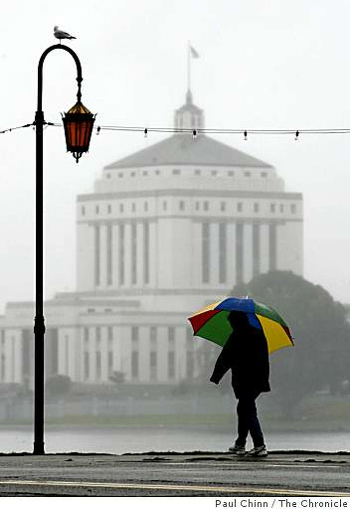 An umbrella-toting woman walks along Lake Merritt not far from the Alameda County Courthouse in Oakland, Calif.
