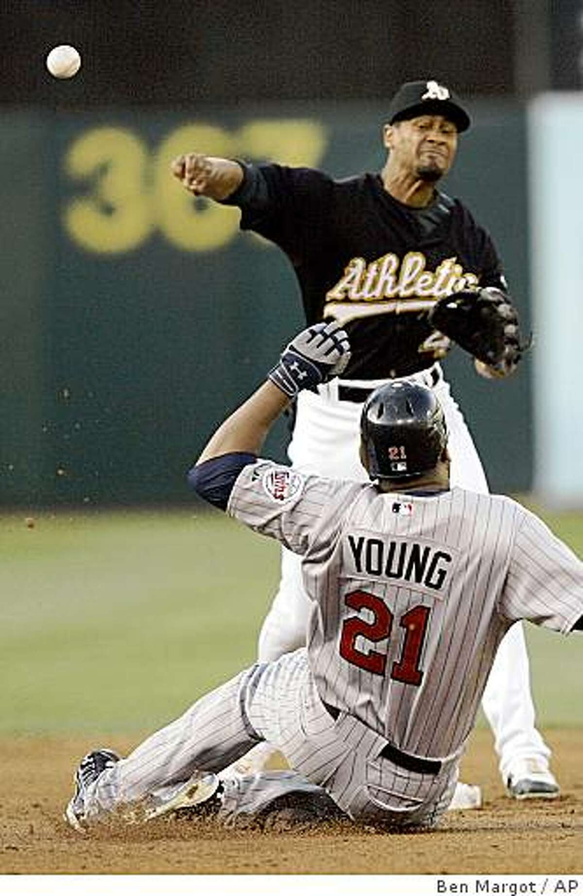 Oakland Athletics second baseman Eric Patterson throws to first base over Minnesota Twins' Delmon Young during the second inning of a baseball game Saturday, Aug. 30, 2008, in Oakland, Calif. Twins' Brendan Harris was safe at first base on the failed double play. (AP Photo/Ben Margot)