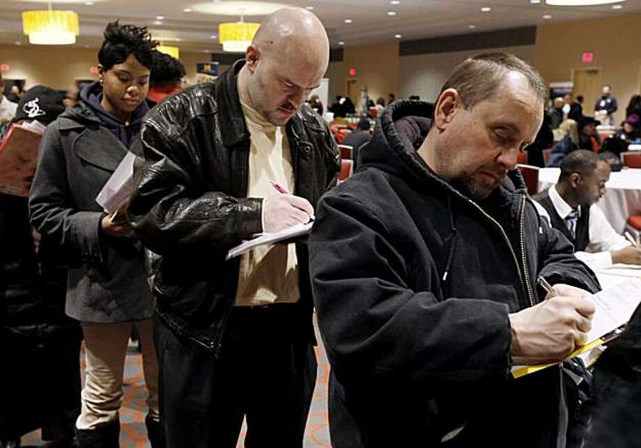 In this Feb. 10, 2010 photo, Sharon Phillips, left, William Wright, center, and Tim Paliwoda, right, all of Detroit, fill out applications while attending a job fair in Detroit. The unemployment rate held at 9.7 percent in February as employers shed fewerjobs than expected, evidence that the job market may be slowly healing. Photo: Paul Sancya, AP