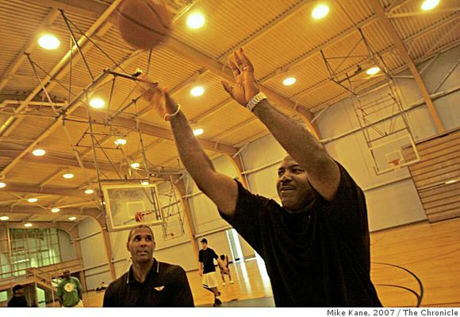 San Francisco Academy of Arts University athletic director Jamie Williams, formerly of the SF 49ers, takes a shot during the school's new basketball team's practice, while basketball head coach Peter Thibeaux looks on at the YMCA gym on Treasure Island in San Francisco, CA, on Thursday, July, day}, 2007. Photo: Mike Kane, 2007, The Chronicle