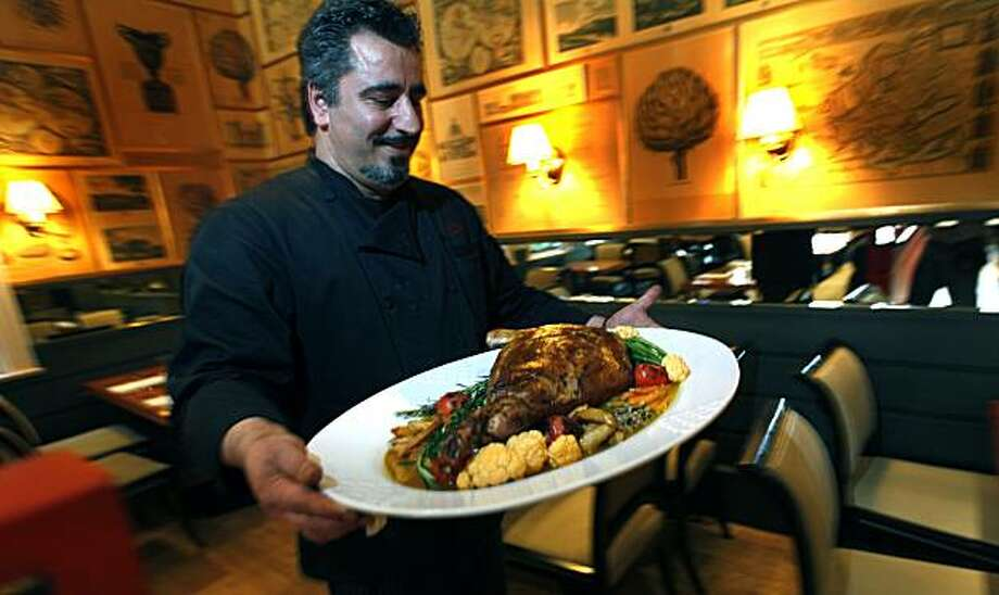 Owner-Chef of Zare at Fly Trap restaurant in San Francisco, Hoss Zare carries a leg of lamb into the dinning room that was prepared for the Persian New Year feast. Thursday March. 4, 2010 Photo: Lance Iversen, The Chronicle