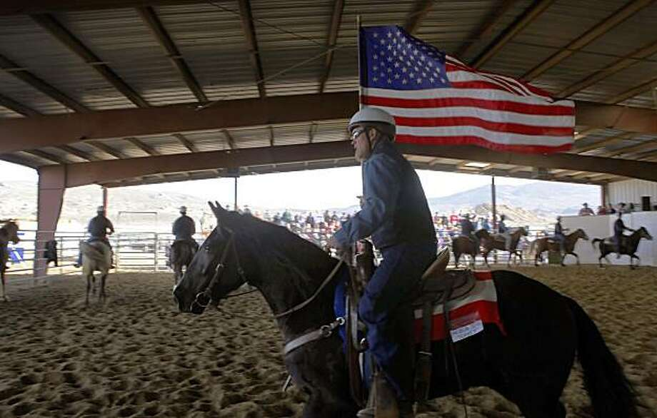 "Robert Railey leads the inmates into the corral carrying the American flag to the song ""Only in America"" by Brooks & Dunn, Saturday Feb. 14, 2010, in Carson City. The inmates parade the horses that they have trained into the corral for the public to see at the start of the auction. Photo: Lacy Atkins, The Chronicle"