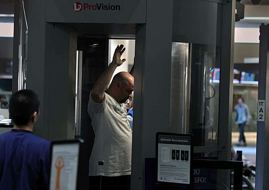 Passengers at SFO International Airport going through security screening using the Whole Body Imager (WBI) in South San Francisco, Ca.,  on Monday,  December 28, 2009.  Using millimeter wave detection the WBI is the only scanner in the bay area which SFO has been using since nine months ago. Photo: Liz Hafalia, The Chronicle