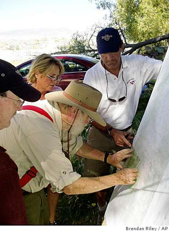 From left to right, search team members Lew Toulmin, Dick Sale, Deb Atwood and Robert Hyman update maps, Saturday, Aug. 30, 2008, at a base camp just west of Hawthorne, Nev., displaying exact areas where searchers had been looking over the weekend for famed aviator and adventurer Steve Fossett, who disappeared Labor Day 2007. (AP Photo/Brendan Riley) Photo: Brendan Riley, AP