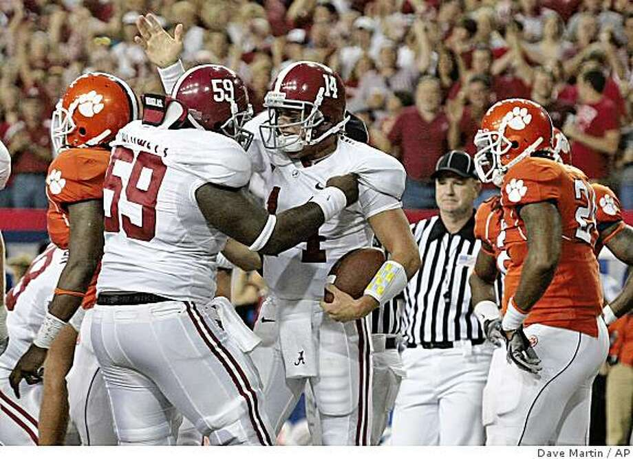 Alabama quarterback John Parker Wilson (14) reacts with teammate Antoine Caldwell after Wilson scored on a two-yard run in the first quarter against Clemson in their football game at the Georgia Dome in Atlanta Saturday, Aug. 30, 2008.  Walking off for Clemson after the score is Brandon Maye, left, and Kevin Alexander, right. (AP Photo/Dave Martin) Photo: Dave Martin, AP