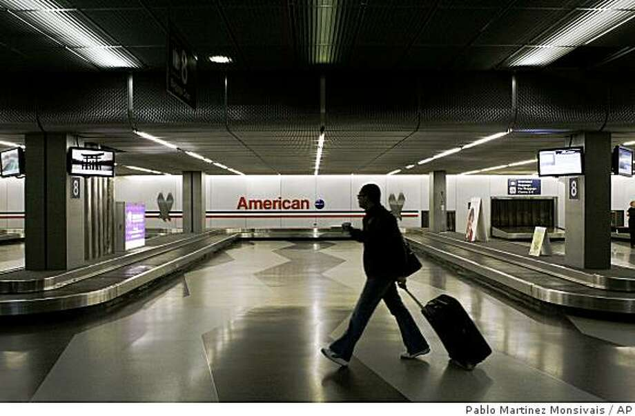 **ADVANCE FOR USE WEEKEND AUG. 30-31, AND THEREAFTER** FILE ** In this April 10, 2008 file photo, a lone traveler walks in the deserted baggage claim area for American Airlines at O'Hare International Airport in Chicago. The grip U.S. airlines have on travelers' wallets is about to get tighter as carriers cut more domestic capacity starting in September due to the high cost of fuel.  (AP Photo/Pablo Martinez Monsivais, file) Photo: Pablo Martinez Monsivais, AP