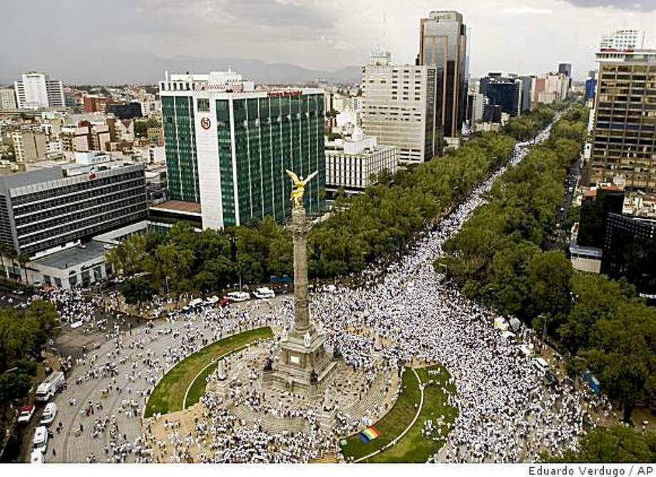 Thousands of Mexicans protest around the Independence monument in Mexico City, against the tide of killings, kidnappings and shootouts sweeping the country, Saturday, Aug. 30, 2008. More than 13 anti-crime groups planned for tens of thousands of people to join marches in all 32 Mexican states Saturday evening, urging people to walk in silence with candles or lanterns. (AP Photo/Eduardo Verdugo) Photo: Eduardo Verdugo, AP