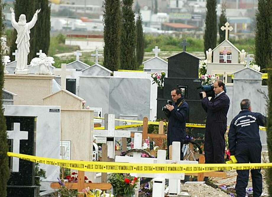 Cypriot police and forensics experts film on March 9, 2010 at the site in a Nicosia suburb where the body of ex-president Tassos Papadopoulos's body was found in another cemetery three months after a grave robbery from his family plot. The body was foundat a cemetery less than five kilometres (three miles) from the robbery site, after an anonymous tip-off from a telephone box. Photo: Stefanos Kouratzis, AFP/Getty Images