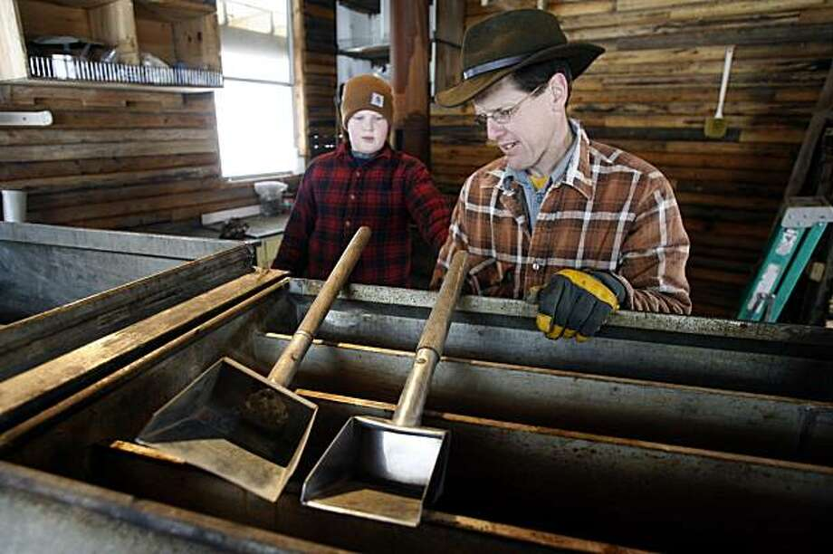 In this Feb. 25, 2010 photo, Eric May, right, and his son, Darin,  prepare his equipment in the sugarhouse at his home in Ira, Vt.  May wasn't too keen on the taste of real maple syrup when he first moved to Vermont but he tapped some trees anyway, borrowing buckets from neighboring farmers. After boiling the sap for 18 hours in a pot over an outside fire, he produced his first quart. Then he was hooked. Photo: Toby Talbot, AP