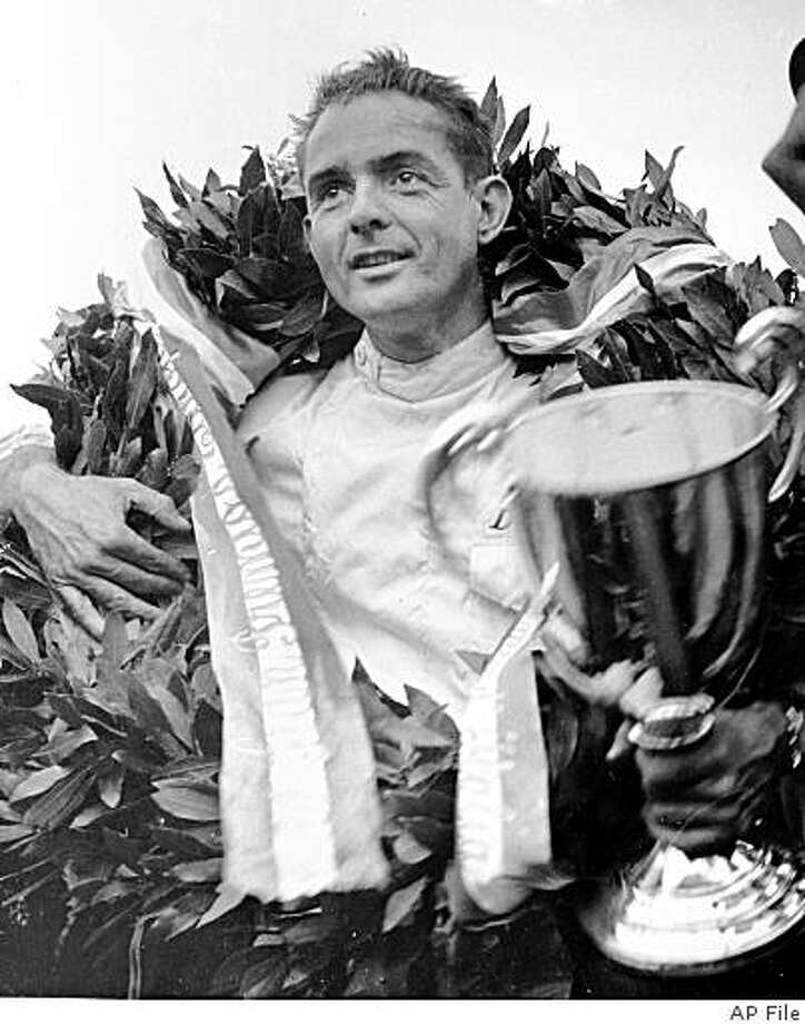 ** FILE ** In this Sept. 6, 1960 file photo, Phil Hill, of the United States, wears a laurel wreath and holds the cup after driving his Ferrari to win the Grand Prix of Europe in Monza, Italy. Hill, the only American-born Formula One champion, died Thursday, Aug. 28, 2008, of complications from Parkinson's disease. He was 81.  (AP Photo/File) Photo: AP File
