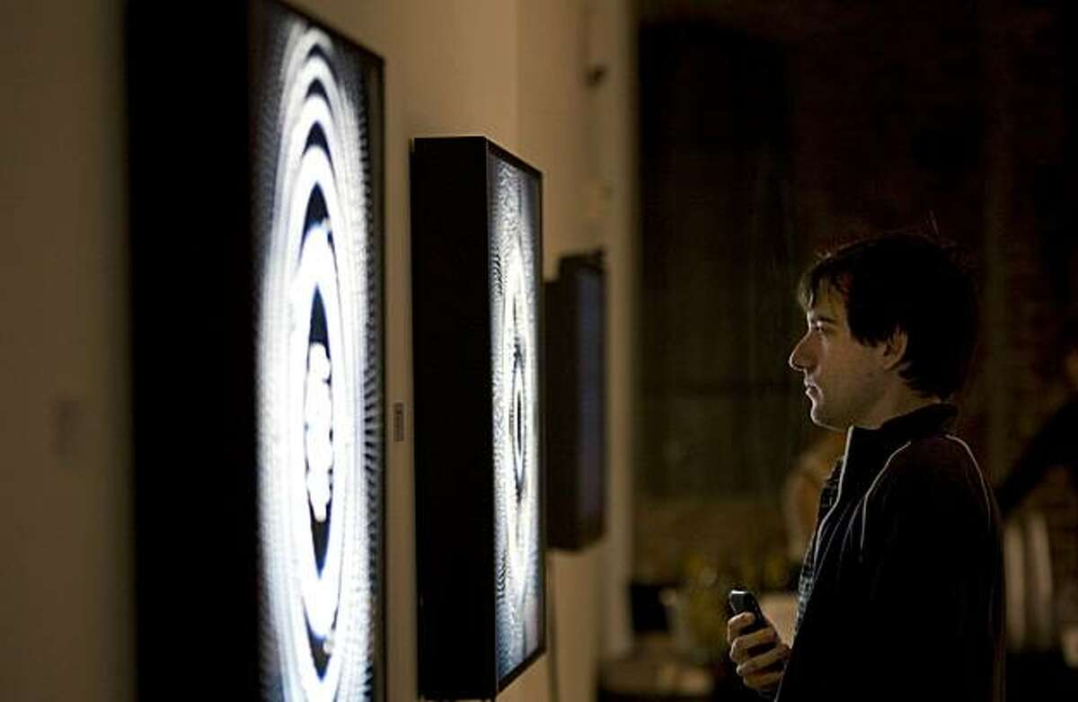 Grey Gomes of San Francisco views Robert Hodgins' piece, Quantam Decoherence, at Gray Area Gallery in the Tenderloin in San Francisco, Calif. on Saturday, Feb. 21, 2010. Showcasing media art, the new gallery is drawing lots of attention from the under-30, Google, iTunes, app-creator set who create computer-generated artwork.