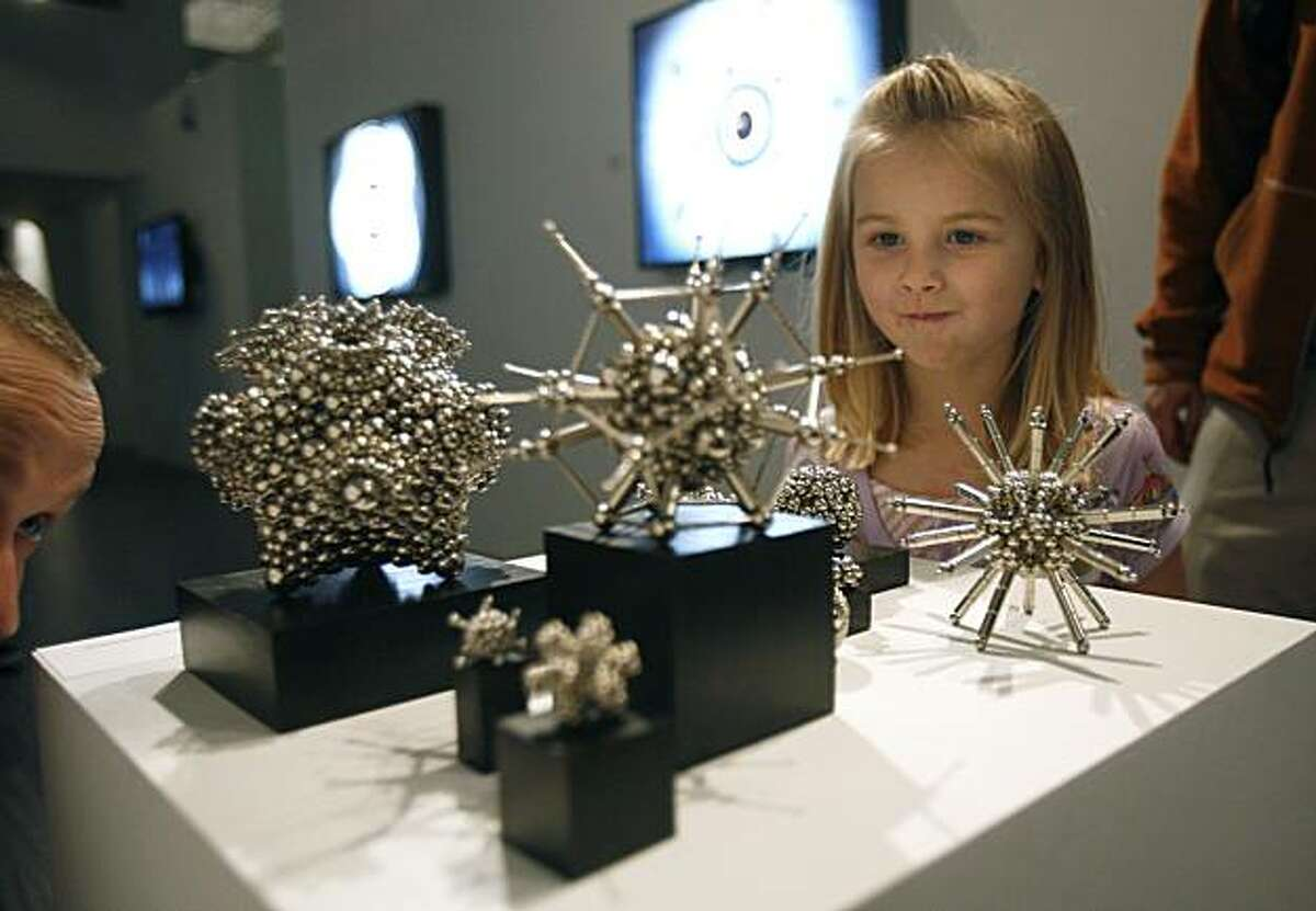 Pica Hering, 4, right, and her father Jason Hering, left, check out Robert Hodgins' magnet sculptures at Gray Area Gallery in the Tenderloin in San Francisco, Calif. on Saturday, Feb. 21, 2010. Showcasing media art, the new gallery is drawing lots of attention from the under-30, Google, iTunes, app-creator set who create computer-generated artwork.