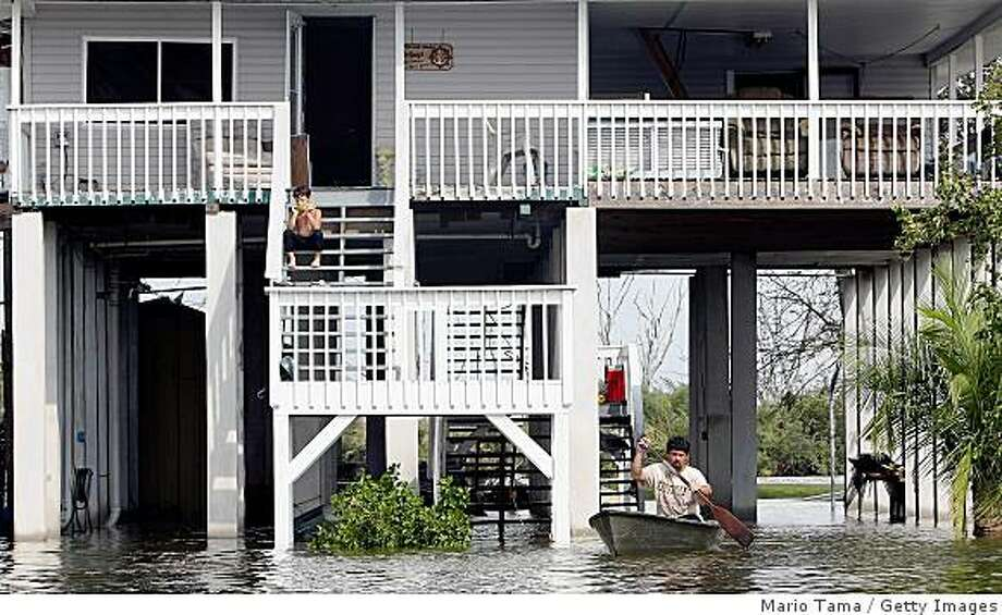 CHAUVIN, LA - SEPTEMBER 2:  Kim Guy (R) paddles away from his home in the floodwaters from Hurricane Gustav as his son James, 7, eats watermelon on the porch September 2, 2008 in Chauvin, Louisiana. Chauvin is located just north of Cocodrie, where Hurricane Gustav made landfall.  (Photo by Mario Tama/Getty Images) Photo: Getty Images