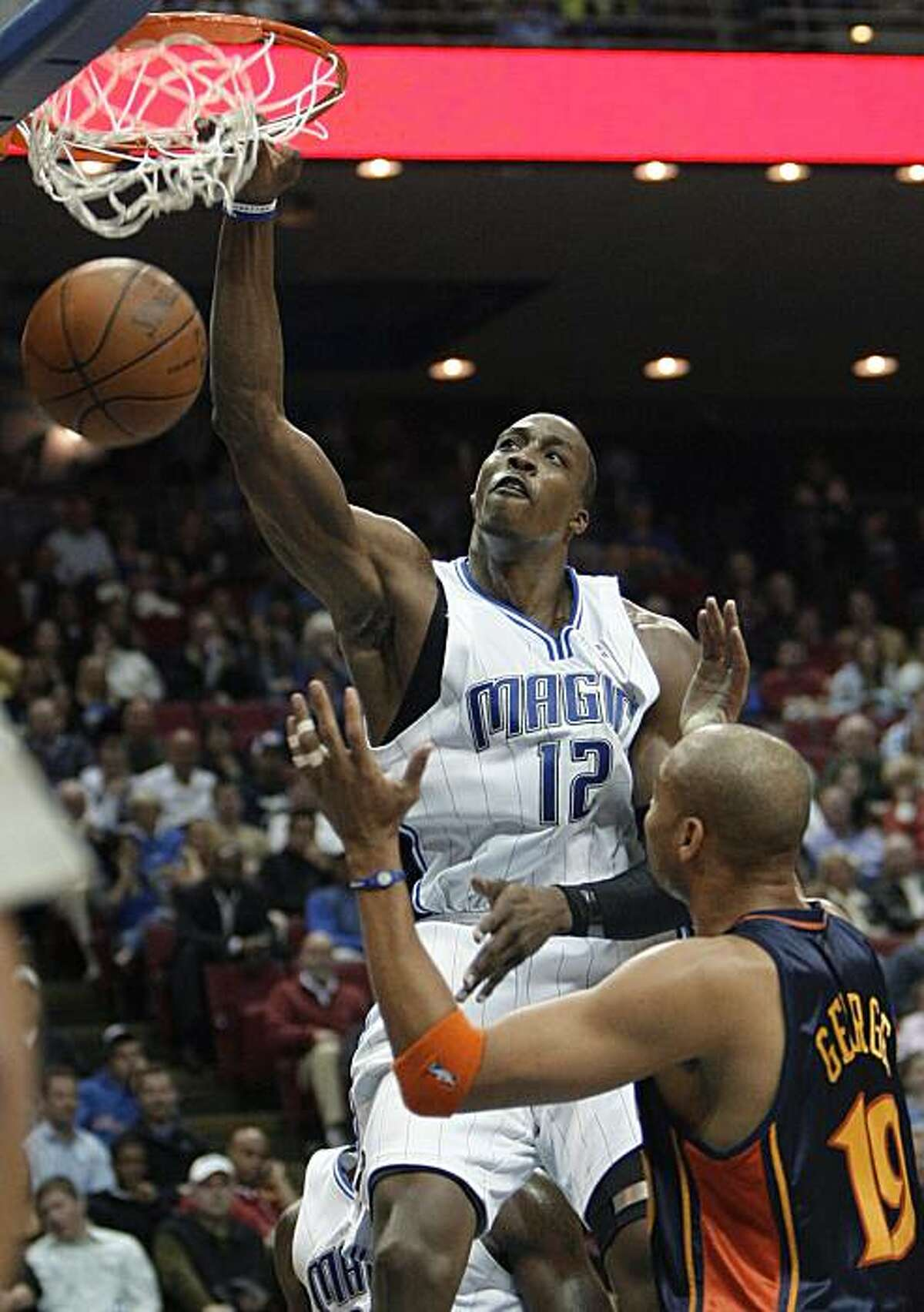 Orlando Magic center Dwight Howard (12) dunks over Golden State Warriors forward Devean George (19) during the second half of an NBA basketball game in Orlando, Fla., Wednesday, March 3, 2010. Orlando won 117-90.