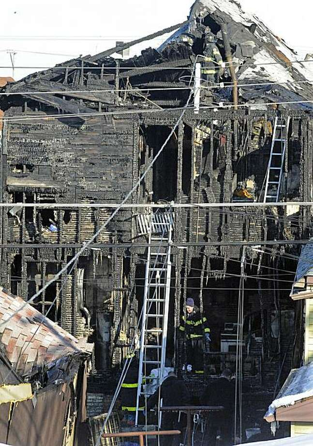 In this photo taken Feb. 14, 2010, firefighters carry out the covered bodies of children from the rear of a burnt building in Chicago.  Seven people died in the fire, including a newborn baby, a 3-year-old and four teenagers. Photo: Al Podgorski, AP