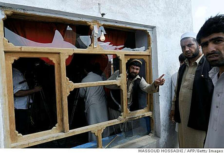Afghan men stand near a broken window, allegedly damaged in a morning raid by international troops, in Kabul on September 1, 2008.  Hundreds of Afghans took to the streets in protest at what they said was the murder of four civilians, including two baby boys, in an early morning raid by international troops. The demonstrators showed journalists the bloodied bodies of the children shot dead with their father on the eastern outskirts of the capital, an AFP reporter said.     AFP PHOTO /Massoud HOSSAINI (Photo credit should read MASSOUD HOSSAINI/AFP/Getty Images) Photo: MASSOUD HOSSAINI, AFP/Getty Images