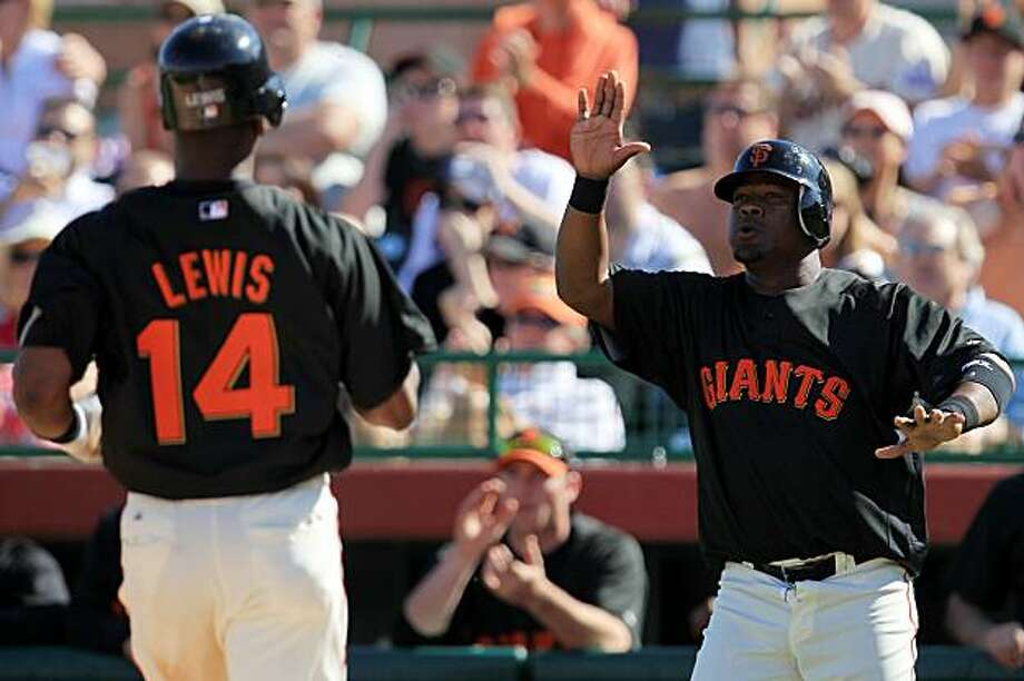 SCOTTSDALE, AZ - MARCH 04: Juan Uribe #5 of the San Francisco Giants celebrates with teammate Fred Lewis #14 after scoring two runs off a double by Eli Whiteside against the Milwaukee Brewers during a spring training game at Scottsdale Stadium on March 4,2010 in Scottsdale, Arizona. Photo: Chris McGrath, Getty Images