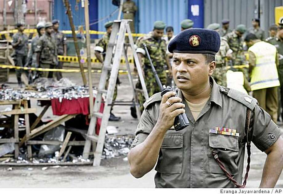A Sri Lankan army officer stands guard, as police investigate at the site of an explosion in Colombo, Sri Lanka, Saturday, Aug. 30, 2008. A bomb blast blamed on separatist Tamil Tigers wounded 45 people in Sri Lanka's capital Saturday, while renewed fighting in the embattled north killed 18 rebels and three soldiers, the military said. (AP Photo/Eranga Jayawardena) Photo: Eranga Jayawardena, AP