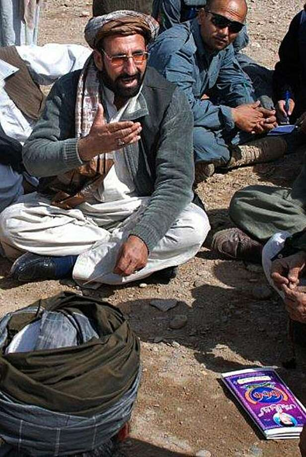 In this Feb. 22, 2010 photo released by the United States Agency for International Development, Abdul Zahir speaks to locals during a shura, or meeting, in Marjah, Afghanistan. Abdul Zahir, appointed as the new civilian chief in Marjah just seized from the Taliban, has a violent criminal record in Germany, but Western officials said Saturday, March 6, 2010, they are not pushing to oust him. Photo: Rory Donohoe, AP