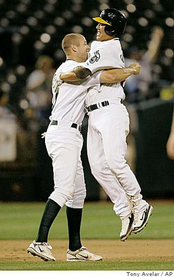 Oakland Athletics Bobby Crosby, left, celebrates with teammate Kurt Suzuki after hitting a single to score the winning run against the Minnesota Twins in the bottom of the ninth inning of a baseball game Thursday, Aug. 28, 2008, in Oakland, Calif. Oakland won 3-2. (AP Photo/Tony Avelar) Photo: Tony Avelar, AP