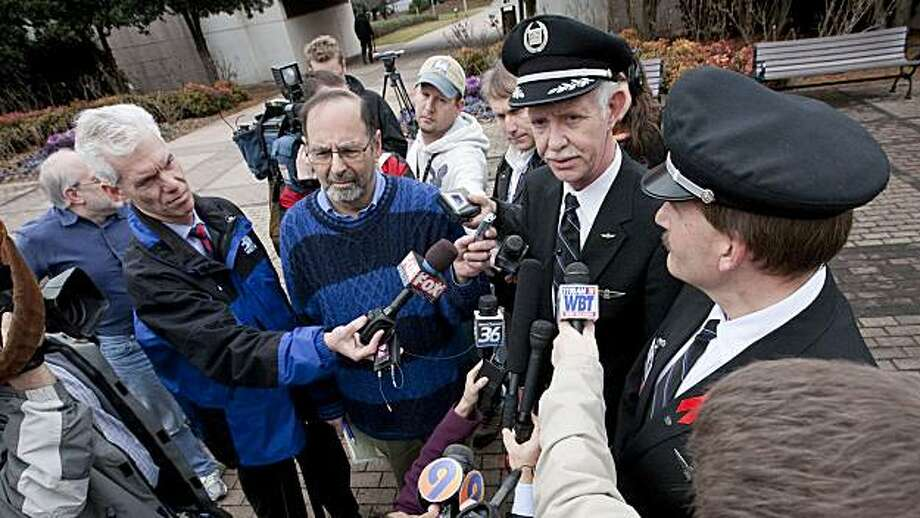 "US Airways pilot Capt. Chesley ""Sully"" Sullenberger, second from right, speaks to reporters at the Charlotte Douglas International Airport in Charlotte, N.C. on Wednesday, March 3, 2010. The pilot who landed a US Airways plane safely on the Hudson River in January 2009 said Wednesday he is retiring after 30 years and plans to spend some of his time pressing for more flight safety. Photo: Jason E. Miczek, AP"