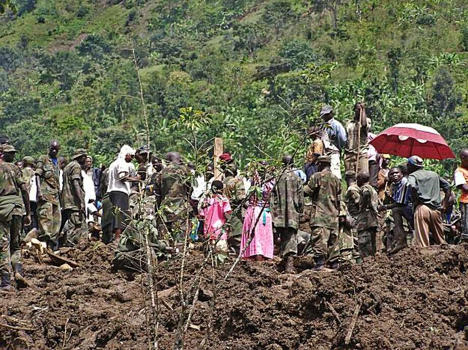 Ugandan military personel and villagers stand on fresh earth following a landslide in eastern Uganda on March 2, 2010 that killed more than 55 people at Mbale District.  A landslide triggered by torrential rain has buried entire villages and left more than 300 people missing in eastern Uganda, where at least 55 people have been killed. Rescue workers began pulling bodies from the mud after the landslide on Monday evening, while the Ugandan Red Cross reported widespread flooding and damage. Photo: Peter Busomoke, AFP/Getty Images
