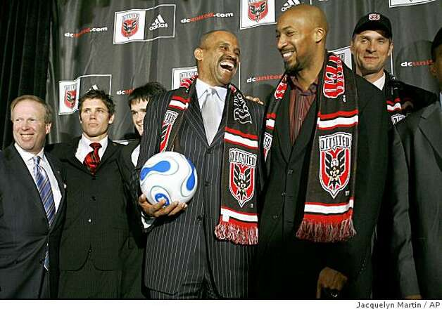 Victor B. MacFarlane, front left, the new majority owner of D.C. United soccer team, jokes with one of the co-owners Brian K. Davis, next to Christian Laettner, far right, after a news conference announcing D.C. United's new ownership in Washington Monday Jan. 8, 2007. At rear left is D.C. United President Kevin Payne. (AP Photo/Jacquelyn Martin) Photo: Jacquelyn Martin, AP