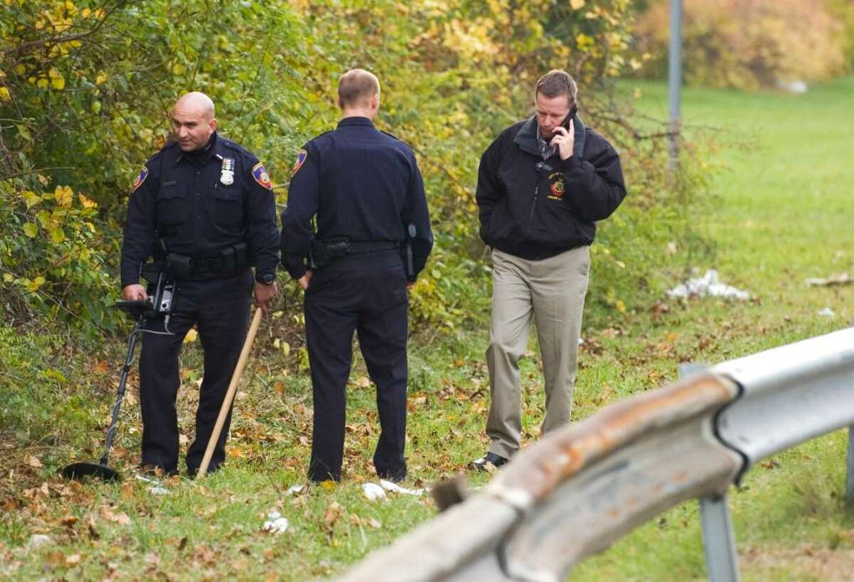 A Stamford police officer, left, uses a metal detector to search for evidence as Lt. Timothy Shaw, right, talks on the phone alongside Northbound I-95 on the Westport/Norwalk border Thursday, after the fatal shooting of Denny Alcantara, 22, of Stamford on Wednesday evening.