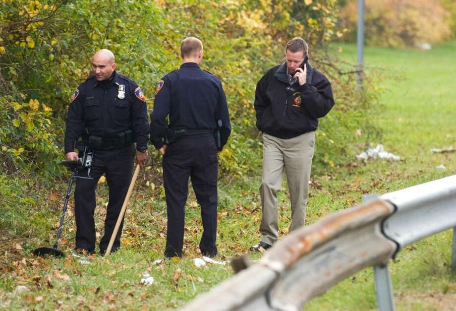 A Stamford police officer, left, uses a metal detector to search for evidence as Lt. Timothy Shaw, right, talks on the phone alongside Northbound I-95 on the Westport/Norwalk border Thursday, after the fatal shooting of Denny Alcantara, 22, of Stamford on Wednesday evening. Photo: Chris Preovolos / Stamford Advocate