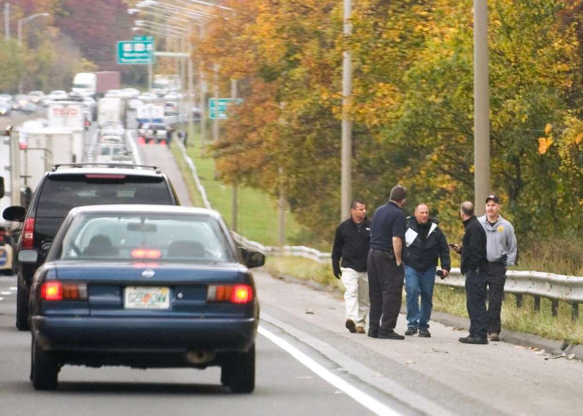 Stamford police officers search for evidence alongside Northbound I-95 on the Westport/Norwalk border Thursday, after the fatal shooting of Denny Alcantara, 22, of Stamford on Wednesday evening.