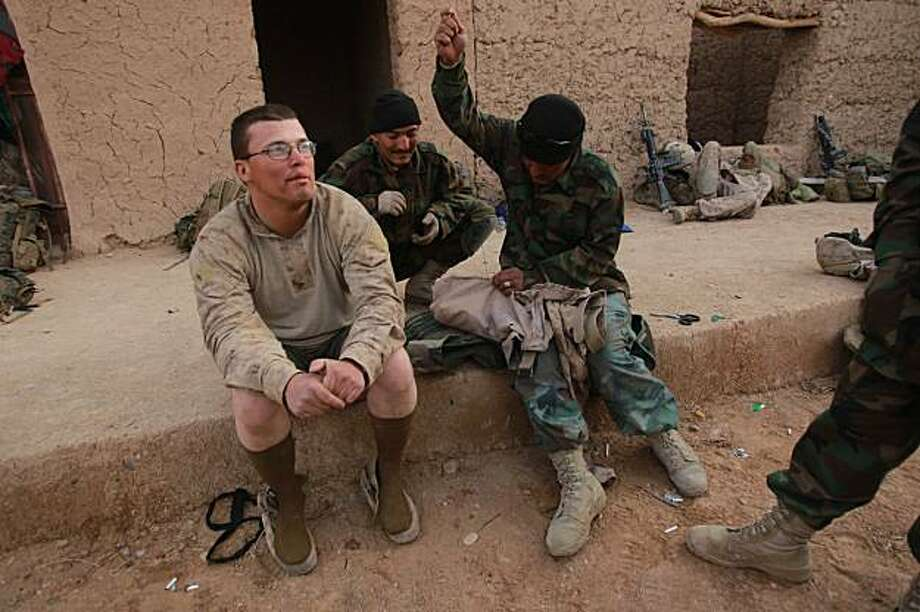 U.S. Marine LCPL William Smith, from 3rd Battalion, 6th Marine Regiment has his torn pants mended by an Afghan National Army soldier at a compound in Marjah in Afghanistan's Helmand province on Saturday Feb. 27, 2010. (AP Photo/David Guttenfelder Photo: David Guttenfelder, AP