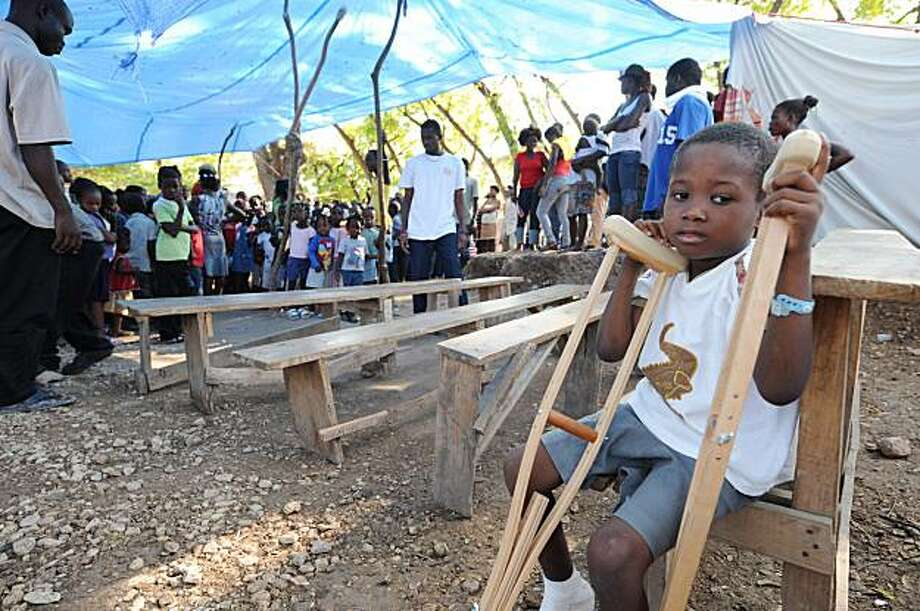 A child rests at a school organized by volunteers in a tent city in Port-au-Prince on March 2, 2010. A 7.0 magnitude Haiti quake, which struck on January 12, 2010 left more than 222,000 people dead and 1.2 million people homeless. Photo: Thony Belizaire, AFP/Getty Images