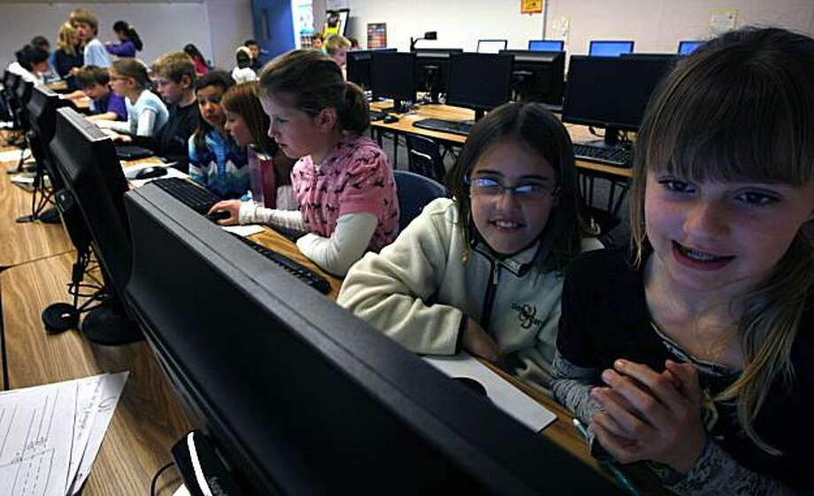 Fourth graders, Olivia Morris right gets help from Jessica Thomas as they work on one of the new computers. Students at Rheem Elementary school in Moraga Ca are working with thin computing machines from Redwood City-based NComputing. One of the benefits is six to ten students can share one PC as they work separately. Photo: Lance Iversen, The Chronicle