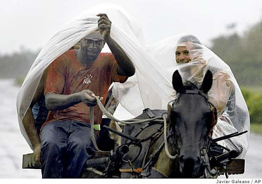 Two men cover themselves from rains caused by the approaching of Hurricane Gustav in Pinar del Rio, Cuba, Saturday, Aug.30, 2008.Gustav swelled to an increasingly fearsome category 3 hurricane with winds of 125 mph (205 kph) as it shrieked toward the heartland of Cuba's cigar industry Saturday, on a track to hit the U.S. Gulf Coast, three years after Hurricane Katrina. (AP Photo/Javier Galeano) Photo: Javier Galeano, AP