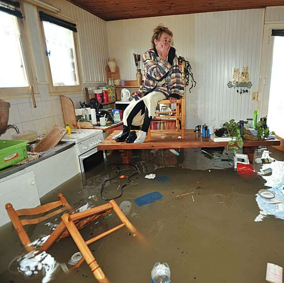A woman seated on a chair atop a table waits for rescuers in her kitchen on February 28, 2010, as a result of heavy floods which swamped her house, in La Faute-sur-Mer western France. Three people drowned in western France's Vendee region, while an 88-year-old woman was found drowned in her home on the isle of Oleron in the Charentes-Maritime further south, police and rescuers said. French authorities had reported Saturday that a man was killed by a falling tree in the southwest Pyrenees region as hurricane-force winds moved across the country after lashing Spain and Portugal. Storms lashing southern Europe killed six more people in France and Spain, authorities reported Sunday, taking to at least nine the death toll from the weekend's violent weather. Photo: Franck Perry, AFP/Getty Images