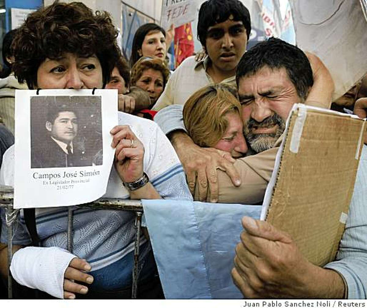 """Human rights activists react outside the courtroom after hearing the verdict that condemned former Argentine Army Gen. Antonio Domingo Bussi to life imprisonment over the disappearance of a provincial senator during the 1976-1983 """"Dirty War"""" dictatorship, in the northern province of Tucuman, August 28, 2008. Bussi, 82, who wept during Thursday's hearing, built a political career after democracy returned to Argentina in 1983 and was elected in 1995 as governor of Tucuman, a sugar- and citrus-growing province that is among the country's poorest. REUTERS/Juan Pablo Sanchez Noli (ARGENTINA)"""